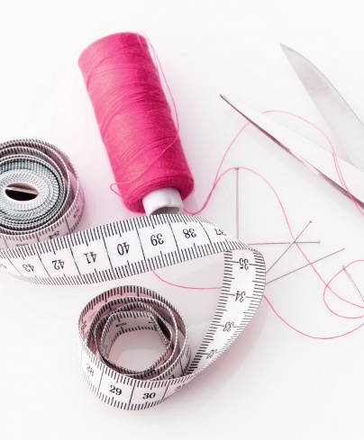 spool of thread, fabric scissors, pins, tape measure