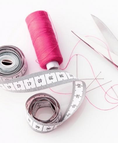 spool of thread, fabric scissors, pins, tape measure